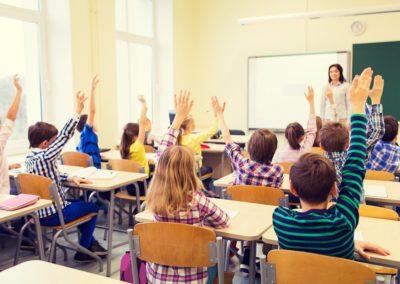 group of school kids raising hands in classroom